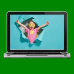 A laptop with an image of a superhero child bursting through a paper wall.